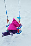 Happy child girl on swing in sunset winter. Little kid playing on a winter walk in nature royalty free stock photos
