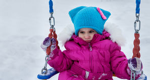 Happy child girl on swing in sunset winter. Little kid playing on a winter walk in nature Stock Photos