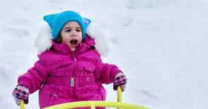 Happy child girl on swing in sunset winter. Little kid playing on a winter walk in nature Royalty Free Stock Image