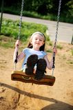 Happy child girl is swinging in the playground Stock Images