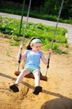 Happy child girl is swinging in the playground Royalty Free Stock Photo