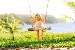 Happy child girl swinging on swing at beach  in summer Stock Photo