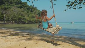 Happy child girl swinging at tropical sandy beach. In slow motion. Cheerful baby amuses at island`s beach stock video footage