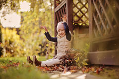 Happy child girl throwing leaves on the walk in sunny autumn garden Stock Photos