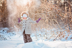 Happy child girl throwing snow in winter sunny forest Stock Image