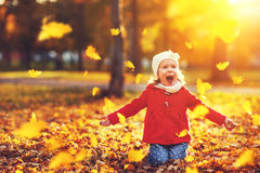Happy child girl throws autumn leaves and laughs Royalty Free Stock Photography