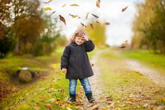 Happy child girl throws autumn leaves and laughs in the park. Royalty Free Stock Photos