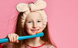 Happy child girl with toothbrush brushes teeth stock photos
