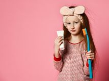 Happy child girl with toothbrush brushes teeth and smiles stock images