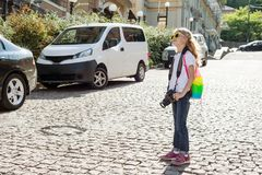 Happy child girl tourist. With a camera, a backpack, travels along the street of city.  Royalty Free Stock Image