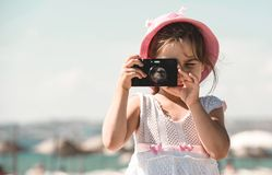 Happy Child Girl Tourist Taking Photos At Sea Side. In Summer stock image