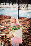 Happy child girl with tulips bouquet having fun on the walk in early spring Royalty Free Stock Photo