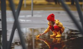 Happy child girl with umbrella and paper boat in   puddle in   a Stock Images