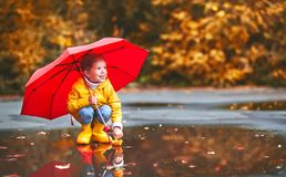 Happy child girl with umbrella and paper boat in   puddle in   a Stock Photography