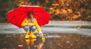 Happy child girl with umbrella and paper boat in   puddle in   a Royalty Free Stock Photography
