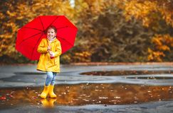 Happy child girl with an umbrella and rubber boots on autumn wal Royalty Free Stock Photo