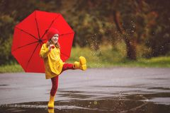 Happy child girl with an umbrella and rubber boots jump in puddle on autumn walk. Happy child girl with an umbrella and rubber boots jump in puddle on an autumn stock image