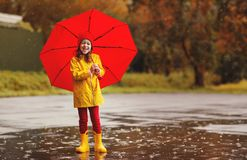 Happy child girl with an umbrella and rubber boots jump in puddl Royalty Free Stock Photo