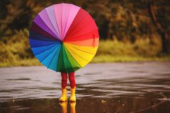 Happy child girl with an umbrella and rubber boots in puddle  on Royalty Free Stock Photo