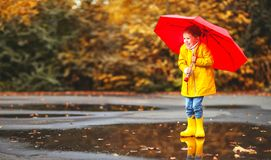 Happy child girl with an umbrella and rubber boots in puddle  on Stock Photography