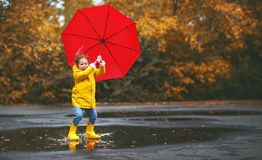 Happy child girl with an umbrella and rubber boots in puddle  on Stock Image
