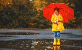 Happy child girl with an umbrella and rubber boots in puddle  on Royalty Free Stock Photography