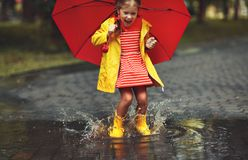 Happy child girl with an umbrella and rubber boots in puddle on Stock Images