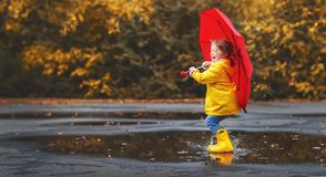 Happy child girl with an umbrella and rubber boots in puddle  on Royalty Free Stock Images