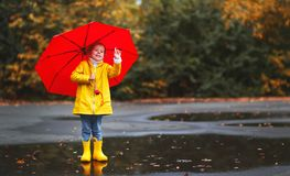 Happy child girl with an umbrella and rubber boots in puddle  on Royalty Free Stock Image