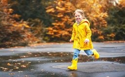 Happy child girl with an umbrella and rubber boots in puddle  on Royalty Free Stock Photos