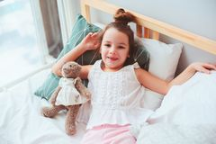 Happy child girl wake up in the early morning in her room. Lying on comfortable bed in cozy homely interior Stock Image
