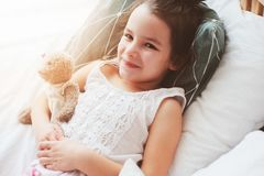 Happy child girl wake up in the early morning in her room Stock Photos