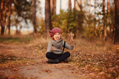 Happy child girl on the walk in autumn forest sitting on the road Stock Photos