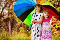 Happy child girl walk with multicolored umbrella under rain royalty free stock photography