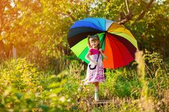 Happy child girl walk with multicolored umbrella under  rain royalty free stock photography