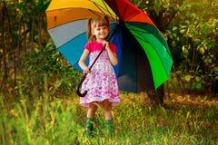 Happy child girl walk with multicolored umbrella under rain stock image