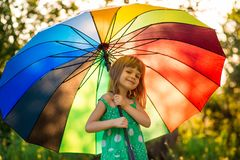 Happy child girl walk with multicolored umbrella under rain royalty free stock photo