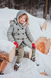 Happy child girl on the walk in snowy winter forest sitting on wood log Royalty Free Stock Photo