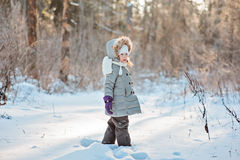 Happy child girl on the walk in winter forest standing and looking out of camera Royalty Free Stock Image