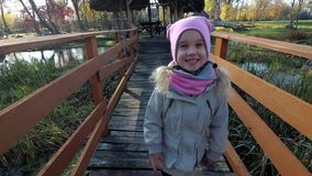 Happy child girl walk on wooden bridge in autumn. River stream in background stock video