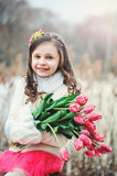 Happy child girl on warm winter forest walk, soft toned. Happy child girl with flowers on warm winter forest walk, soft toned, birthday celebration in winter Royalty Free Stock Photography