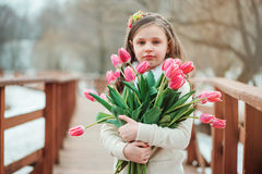 Happy child girl on warm winter forest walk, soft toned. Happy child girl with flowers on warm winter forest walk, soft toned, birthday celebration in winter Stock Photo