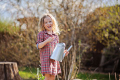Happy child girl with watering can in spring garden Royalty Free Stock Photos