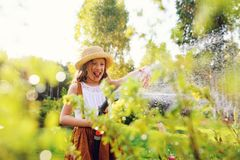 Happy child girl watering flowers with hose in summer garden. Holding water sprinkler, playing outdoor stock photos