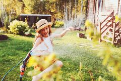 Happy child girl watering flowers with hose in summer garden. Holding water sprinkler, playing outdoor stock photography