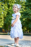 Happy child girl in white gown posing, childhood concept, summer season in city park Stock Image