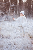 Happy child girl in white outfit on the walk in winter snowy forest Royalty Free Stock Photography