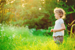 Happy child girl in white shirt on the walk on summer sunny field Royalty Free Stock Images
