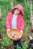 Happy child girl with wild edible wild mushrooms on wooden plate Royalty Free Stock Photos