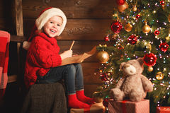 Happy child girl writes letter to Santa Claus at the Christmas t Royalty Free Stock Photography